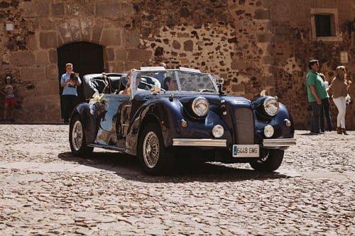 Recién casados conduciendo coche clásico